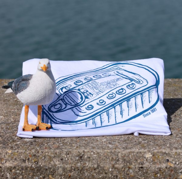 fish mish white t-shirt with tin can navy cketch print folded up and placed on a wall by the sea with a model seagull beside it